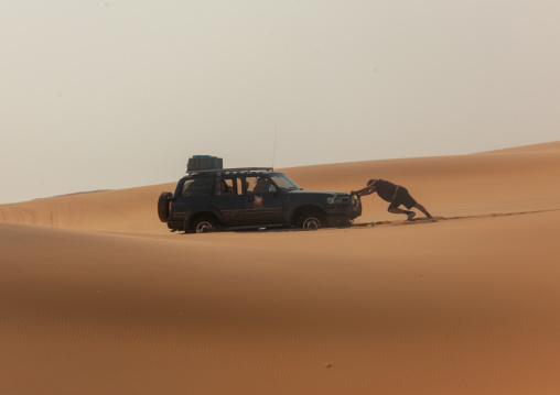 Man pushing a broken down car in the namib desert, Namibe Province, Iona National Park, Angola