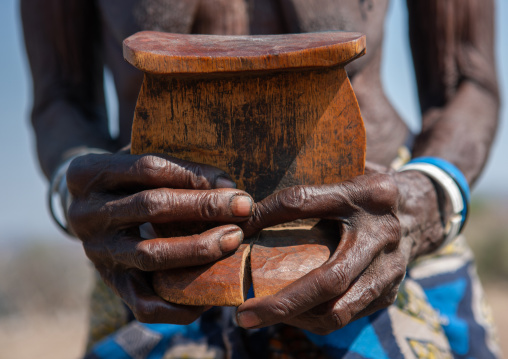 Muhacaona tribe woman holding an old headrest, Cunene Province, Oncocua, Angola