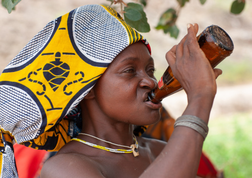 Mucubal tribe woman drinking a beer, Namibe Province, Virei, Angola