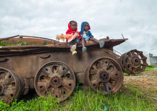 Angolan children playing on a tank wreck, Huambo Province, Huambo, Angola