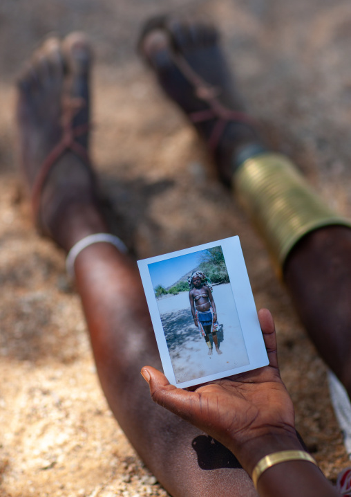 Mucubal tribe woman holding a polaroid of herself, Namibe Province, Virei, Angola