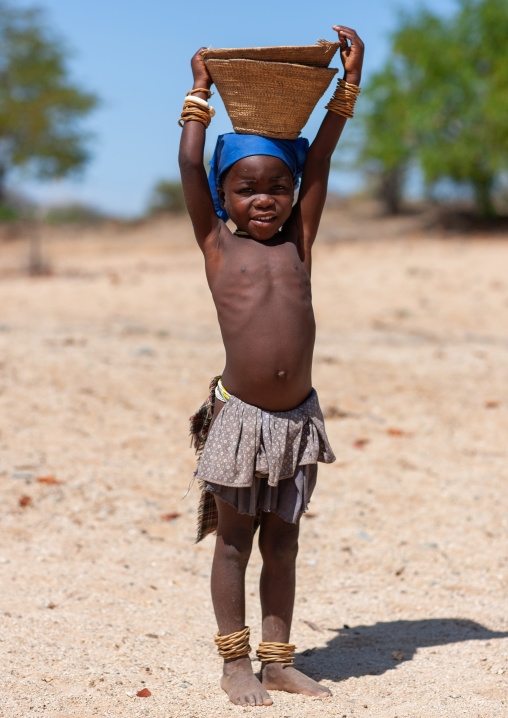 Mucubal tribe girl carrying a basket on head, Namibe Province, Virei, Angola