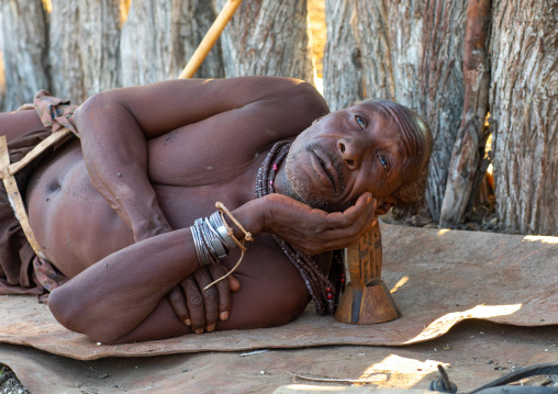 Himba tribe old man resting with his wooden pillow, Cunene Province, Oncocua, Angola