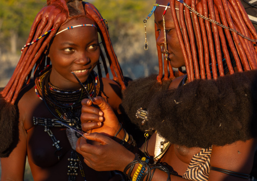 Himba tribe women looking at polaroids, Cunene Province, Oncocua, Angola