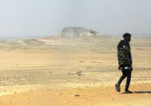 Angolan man walking in the desert, Cunene Province, Curoca, Angola