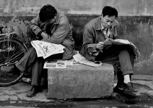 Men Reading Newspapers In A Hutong Street, Beijing China