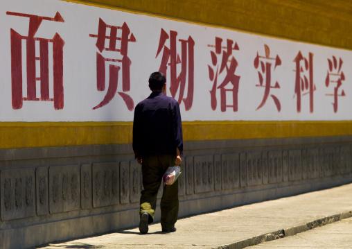 Man Walking Along A Wall With Chinese Script, Dali, Yunnan Province, China