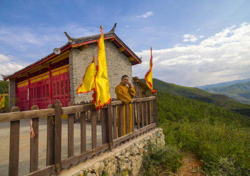 Monk Talking On Mobile Phone In Front Of Temple Over A Valley, Lijiang Area, Yunnan Province, China