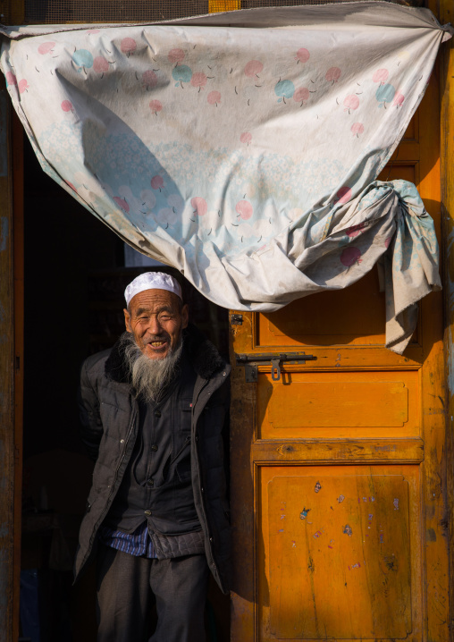 Salar ethnic minority old man at the entrance of his house, Qinghai Province, Xunhua, China