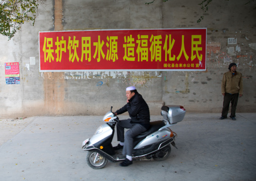 Salar ethnic minority man on a scooter passing in front of a chinese propaganda poster about saving water, Qinghai province, Xunhua, China