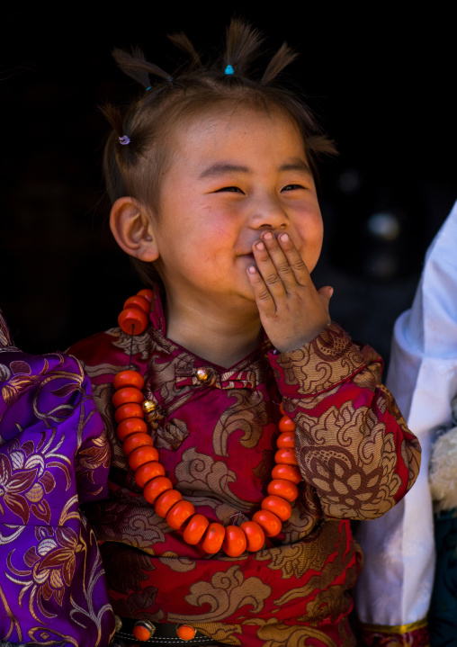 Laughing tibetan child girl with a huge necklace, Tongren County, Rebkong, China
