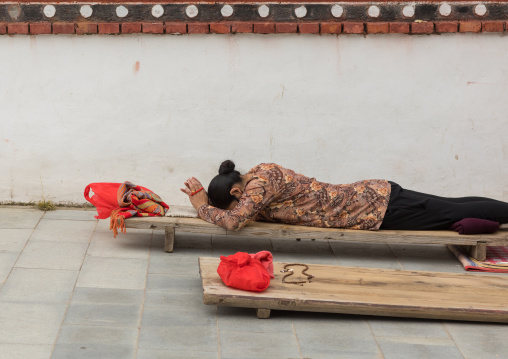 Tibetan pilgrim woman praying and prostrating in Hezuo monastery, Gansu province, Hezuo, China