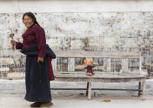 Tibetan nomad woman holding a prayer wheel in her hand, Gansu province, Labrang, China