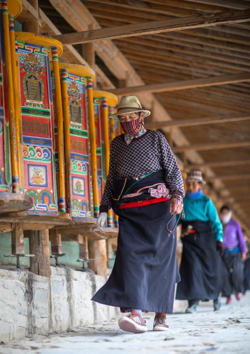 Tibetan pilgrims turning huge prayer wheels in Labrang monastery, Gansu province, Labrang, China