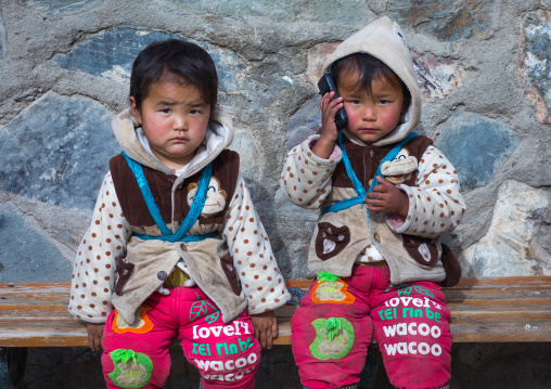 tibetan Children sit on a bench and playing with a mobile phone, Gansu province, Labrang, China