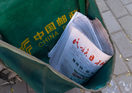 China post mewspapers in a delivery bicycle, Gansu province, Linxia, China
