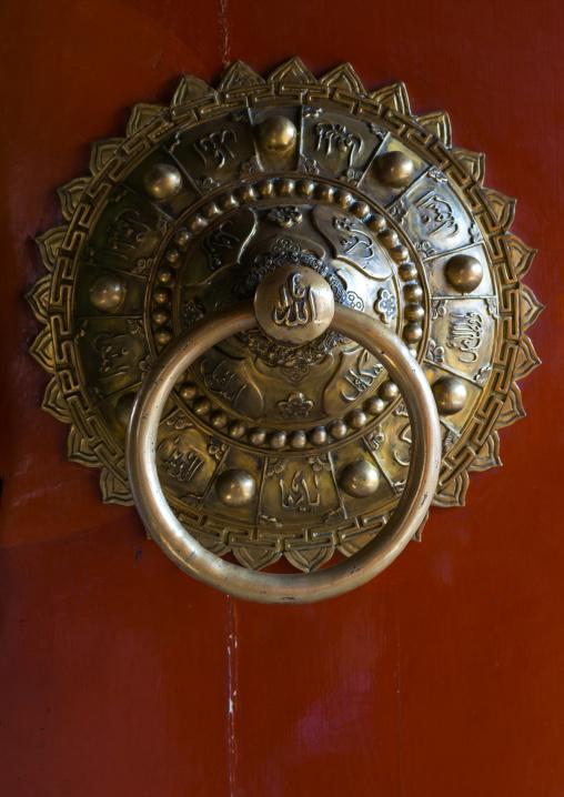 Ornate knocker with arabic scripts on traditional door in Yu Baba Gongbei islamic shrine complex, Gansu province, Linxia, China