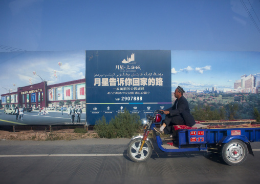 old man passing in front of Advertisement For New Real Estate, New Town Of Kashgar, Xinjiang Uyghur Autonomous Region, China