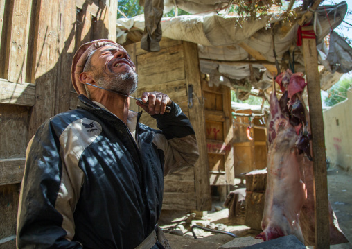 Butcher joking with a knife in the market, Badakhshan province, Ishkashim, Afghanistan