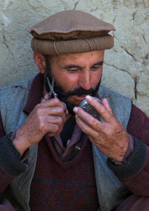 Afghan man cutting his beard in the street, Badakhshan province, Ishkashim, Afghanistan