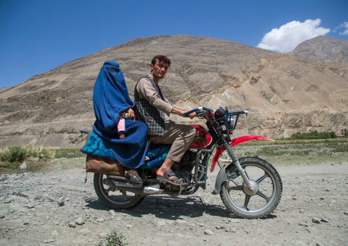 Afghan man riding a motorcycle with his wife wearing a burka, Badakhshan province, Qazi deh, Afghanistan