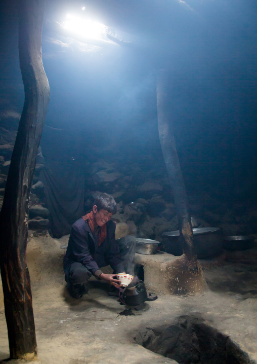 Wakhi teenage boy preparing salty milk tea inside his house, Big pamir, Wakhan, Afghanistan