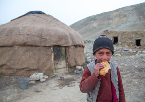 Wakhi nomad boy eating bread in front of his yurt, Big pamir, Wakhan, Afghanistan
