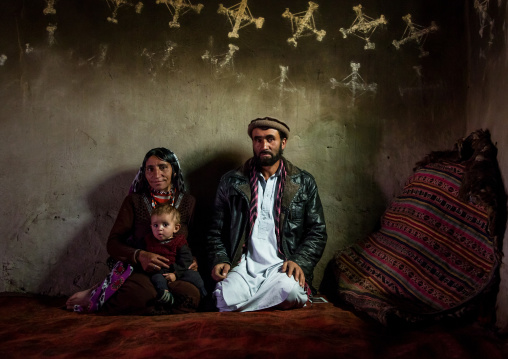 Afghan family inside their traditional pamiri house with the walls decorated for nowruz, Badakhshan province, Zebak, Afghanistan