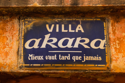 """Benin, West Africa, Porto-Novo, villa akara panel with the name of the house and a french proverb below """"better late than never"""""""