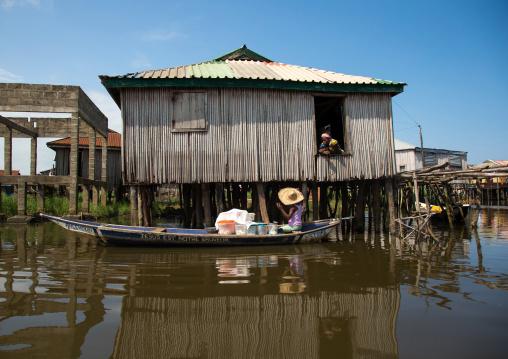Benin, West Africa, Ganvié, boat passing in front of the stilt house on lake nokoue
