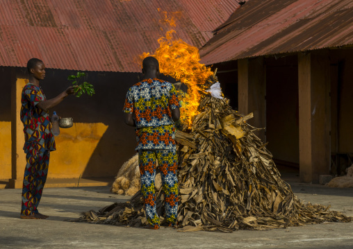 Benin, West Africa, Porto-Novo, men putting fire to a zangbeto guardian of the night in the royal palace