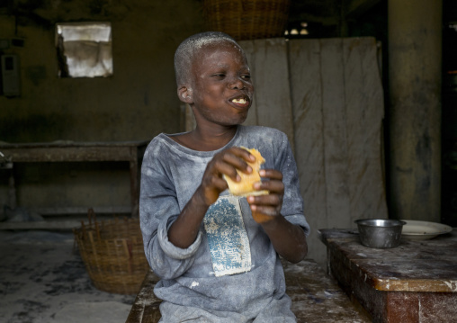 Benin, West Africa, Porto-Novo, boy working in a mill with his face coverded with flour