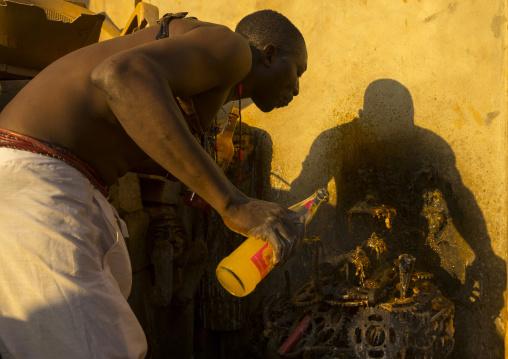 Benin, West Africa, Bonhicon, kagbanon bebe voodoo priest drinking orange juice and spitting it on ogun god altar made with pedaliers biking