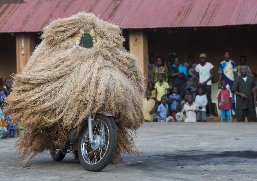 Benin, West Africa, Porto-Novo, zangbeto guardian of the night spirit riding motorcycle in the royal palace