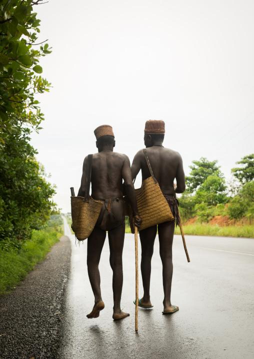 Benin, West Africa, Taneka-Koko, traditional healers walking on a concrete road