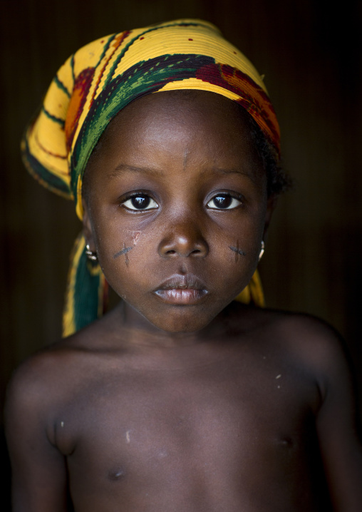Benin, West Africa, Onigbolo Isaba, holi tribe girl with traditional facial tattoos and scars portrait