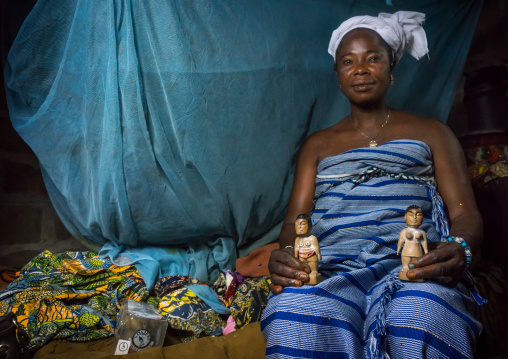 Benin, West Africa, Bopa, miss hounyoga with the carved wooden figures of her dead twins zinsou the boy and zinhoue the girl