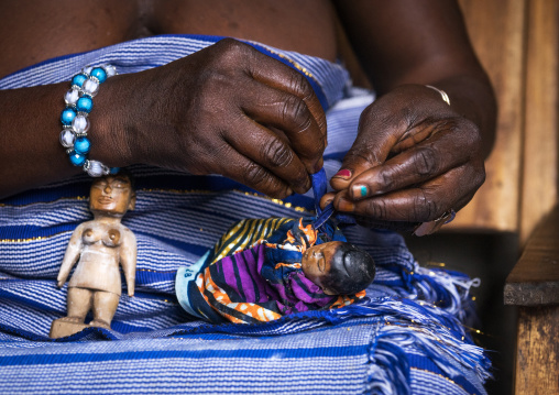 Benin, West Africa, Bopa, miss hounyoga dressing the carved wooden figures of her dead twins