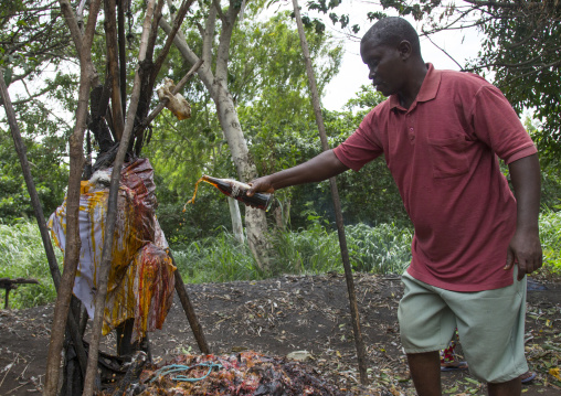 Benin, West Africa, Dankoly, a man putting coca cola on a voodoo shrine as offerings to the spirits