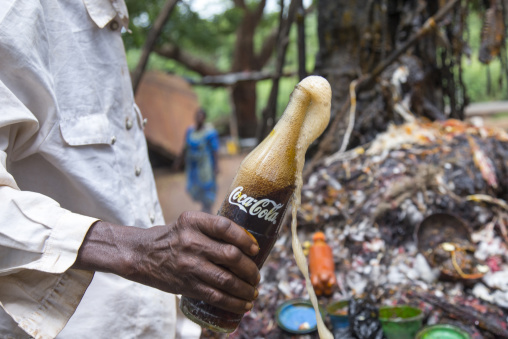 Benin, West Africa, Dankoly, a priest putting coca cola on a voodoo shrine to make an offering to the spirits