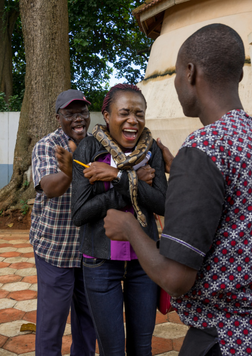 Benin, West Africa, Ouidah, woman screaming as a man puts a snake around her neck in the python temple