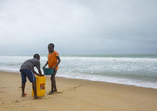 Benin, West Africa, Cotonou, children collecting sea water