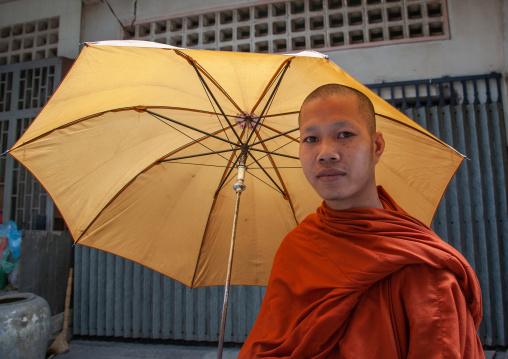 Cambodian monk walking in the street with umbrella, Phnom Penh province, Phnom Penh, Cambodia