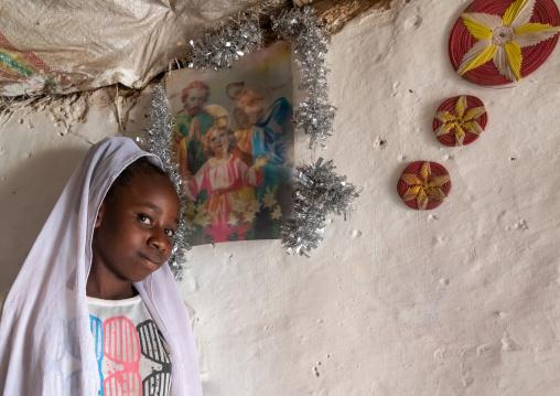 Eritrean Kunama tribe teenage girl in front of a religious poster, Gash-Barka, Barentu, Eritrea