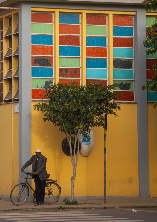 Old eritrean man with his bicycle in front of the multi sport bowling building, Central region, Asmara, Eritrea