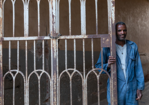 Eritrean man standing at the iron gate of an old art deco building from the italian colonial times, Central region, Asmara, Eritrea