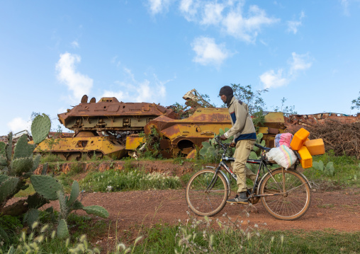 Eritrean man riding a bicycle in front of the military tank graveyard, Central region, Asmara, Eritrea