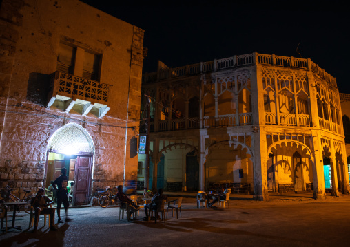 Eritrean men in an open air restaurant in front of ottoman architecture buildings, Northern Red Sea, Massawa, Eritrea