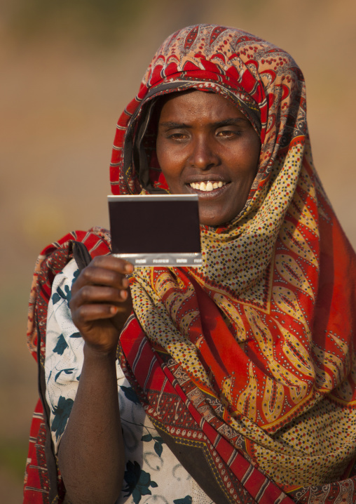 Portrait of a woman with toothy smile seing herself on picture for the first time, Dire dawa, Ethiopia