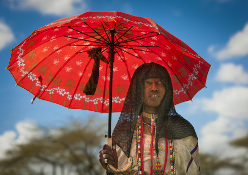 Karrayyu Tribe Woman With Black Headscarf And Colourful Necklaces Under A Red Umbrella, Metahara, Ethiopia